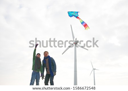 Father and son flying kite on winter day near wind turbines