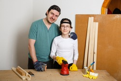 Father and son grind board or plywood with grinder. Teenager learns to work with grinder. Carpenter working in workshop. Renovation DIY work. Beginner skills. Handmade concept. New normal. Stay home