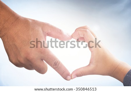 Father and son hands up to blue sky in the shape of a heart around the sun. Creation, Love, Happy Valentine Day, God and Adam, Holy Bible, Health Care, World Cancer, Romantic, CSR, Kid, Child concept.