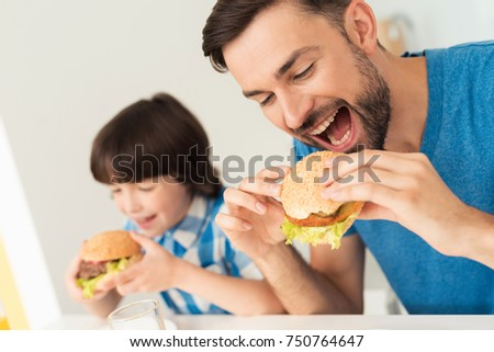 Father and son have breakfast in the light kitchen. They are in their house together. They eat a hamburger. On the table is a glass of juice.