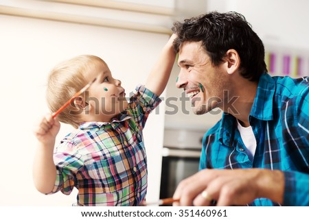 Father and son having a good time. Kid is painting father\'s face with watercolors. Shallow depth of field.
