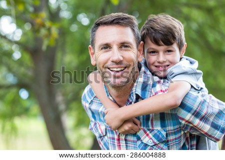 Father and son having fun in the park on a sunny day