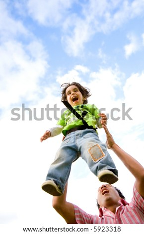 father and son having fun together outdoors in front of a blue sky