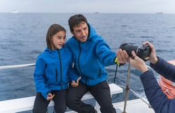 Father and son having their portrait taken by a photographer on top of a boat.