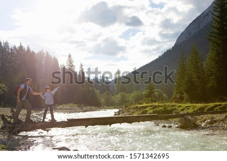 Father and son hiking and crossing river together in mountains