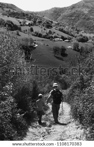 Father  and son hiking in picturesque French Basque country. Back view. Natural lifestyle concept. Black and white photo.