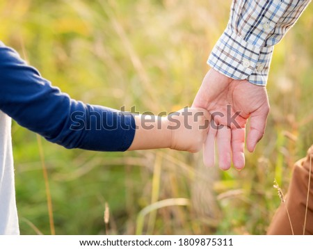 Father and son hold hands. Emotional and moral support. Kid holds daddy's finger. Golden hour outdoors. Natural summer or autumn background. Foto d'archivio ©