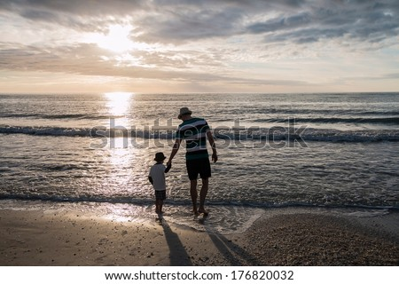 Father and son holding hands in front of the sunset at the beach wearing shorts and a hat