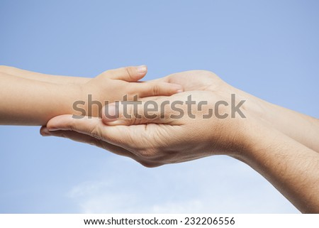 Father and son, holding hands on sky background.
