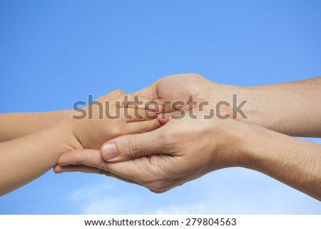 father and son holding hands on sky with clouds background