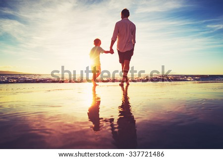 Father and Son Holding Hands Walking Together on the Beach at Sunset #337721486
