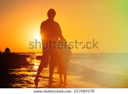 father and son hug at sunset beach