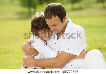 Father and son hugging and playing together in green nature