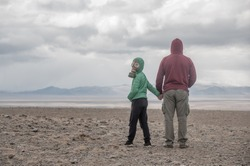 father and son in a gas mask in the desert steppe. Apocalypse postnuclear Doomsday scenario.