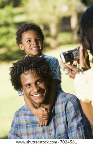 Father and son in park being photographed with digital camera. - stock photo