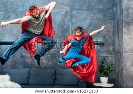 father and son in superhero costumes jumping on sofa at home
