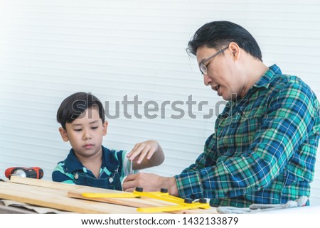 Father and Son is learning to work on wood work with tools for family togetherness concept
