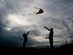 father and son launching a kite at beautiful sunset