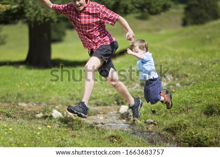 Father and son leaping over stream in countryside