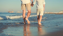 Father and son legs on the sea surfline close up image