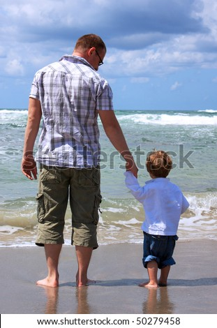 Father and son look at the sea