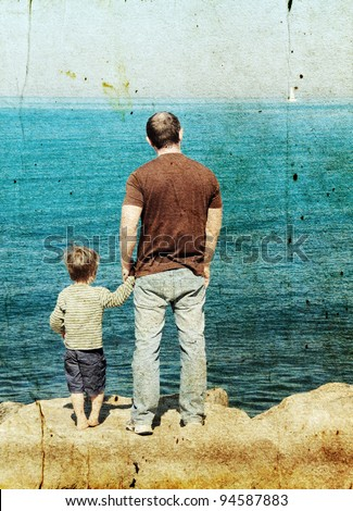 Father and son looking at a white sail in the sea. Photo in old image style.