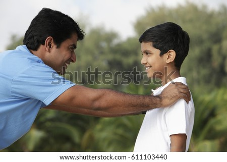Father and son looking at each other and smiling outdoors.
