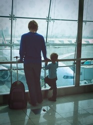 father and son looking at planes while waiting in the airport