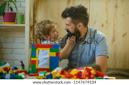 Father and son looks at each other. Little boy touches parent's berad. Asking for something. Development and education. Plastic bricks for children, young age. Friendship with son. Father upbringing #1147674104