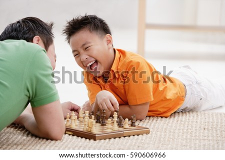 Father and son lying on floor, playing chess, laughing