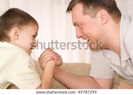 Father and son lying on the carpet and fight on his hands #49787299