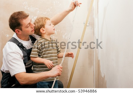 Father and son measuring a dry wall in their home with a folding rule and a bubble level