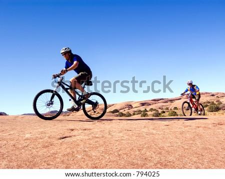 Father and son mountain bike near Moab, Utah