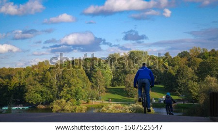 father and son on a bicycle from the back against the backdrop of beautiful nature in the park. Family outdoor activities, activity and sports