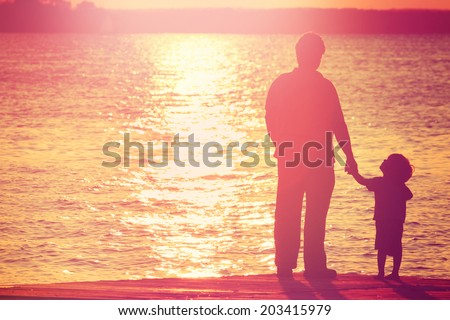 Father and son on a dock at sunset boy looking up at his father