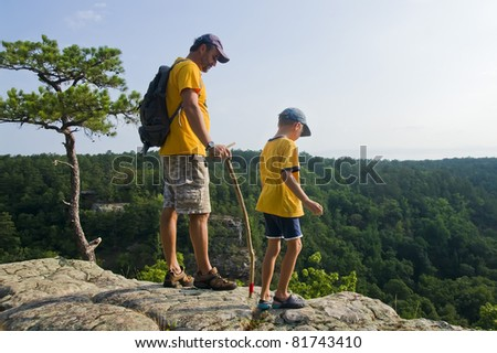 Father and son on a mountain top looking at the path