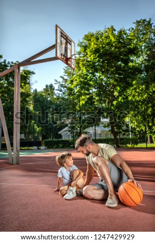 Father and son on the basketball court near the house