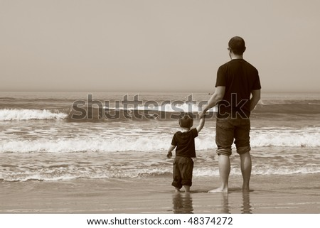 Father and son on the beach. They stand in the water and watch the sea.