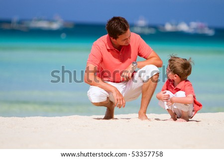 Father and son on tropical white sand beach