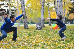 Father and son play with ball in autumn park. Happy family play soccer in public park