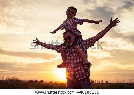 Father and son playing at the park at the sunset time. People having fun on the field. Concept of friendship forever and of summer vacation. #440186131