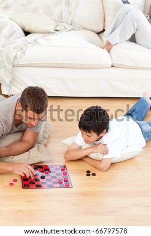 Father and son playing checkers together lying on the floor at home - stock photo