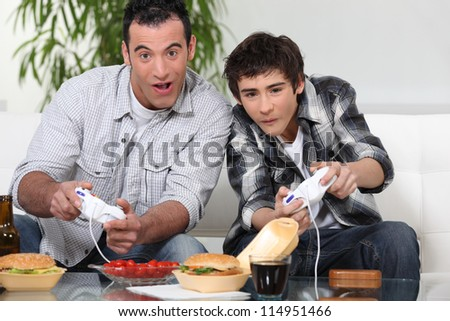 Father and son playing computer games and eating junk food