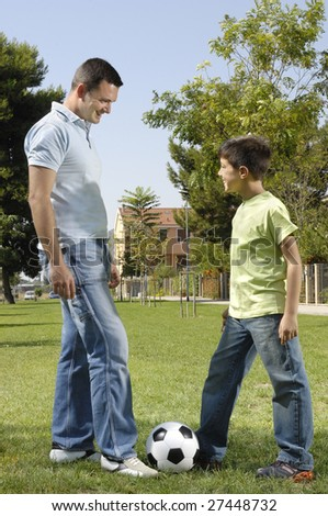 father and son playing football in urban park, concept of entertainment and education