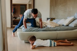 Father and son playing hide and seek in bedroom. Little boy hiding by the bed with father searching him. Family playing games inside their home.