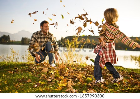 Father and son playing in autumn leaves near lake