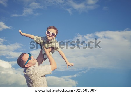 Father and son playing in the park  at the day time. Concept of friendly family. Picture made on the background of blue sky. #329583089