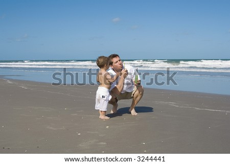 Father and son playing on a beach with bubbles.