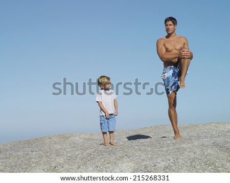 Father and son (4-6) playing on rock near beach, smiling, man in swimming shorts standing on one leg