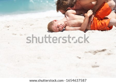 Father and son (7-9) playing on sandy beach